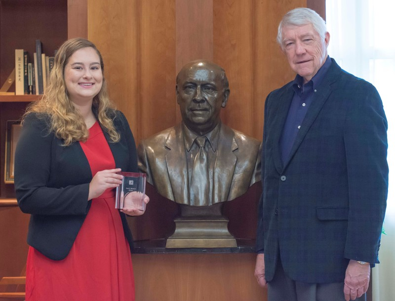 Bickley award winner Laura LePere, left, and Dr. William H. Rabel, John and Mary Louise Loftis Bickley Endowed Teaching Professor of Insurance, pose near a bust of Dr. John S. Bickley in the Insurance Hall of Fame Museum