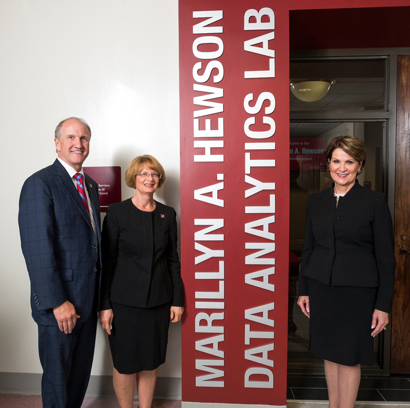 Marillyn A. Hewson stands at the entrance to the lab named in her honor with University of Alabama President Stuart R. Bell and Culverhouse Dean Kay M. Palan.