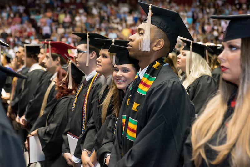 Graduate smiling into the camera at graduation ceremony