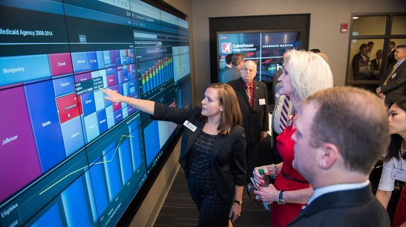 Experts watch the digital trends on a video board.