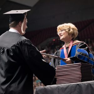 Dean Palan hands a degree to a student at graduation