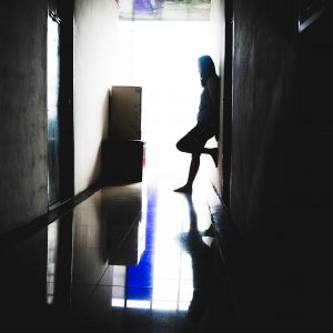 Woman standing in dark hallway