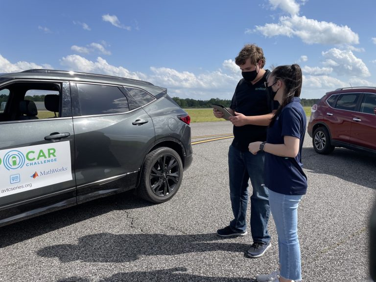 Members of the UA EcoCAR Mobility Challenge team perform tests on their vehicle.